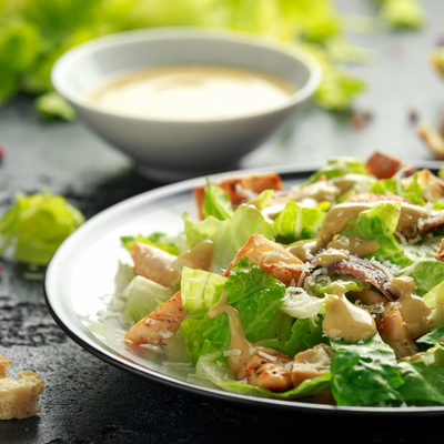 Caesar salad is a fresh, leafy dish that contains romaine lettuce, croutons, cheese, and caesar salad dressing.