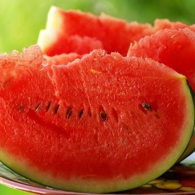 Watermelon is a large fruit that grows on the ground and is usually an oval shape.