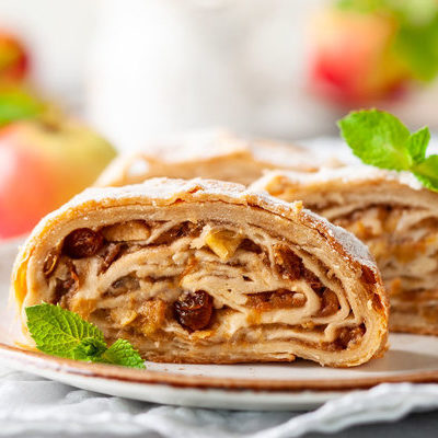 Apple strudel (or Apfelstrudel) is an Austrian dessert made of layered pastry with a grated apple filling inside.