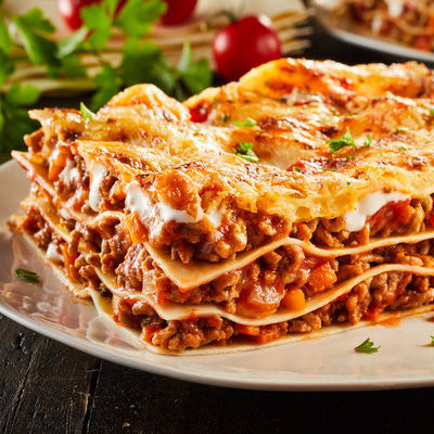 Lasagna is a prepared dish of Italian origin that includes stacked layers of pasta, tomato and bechamel sauces, meat, vegetables, and cheese.