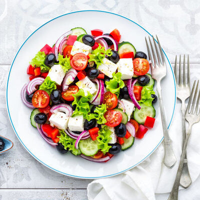 A Greek salad is a salad which consists of tomatoes, cucumbers, onions, olives, and feta cheese, although it can contain seasonings and herbs, as well.