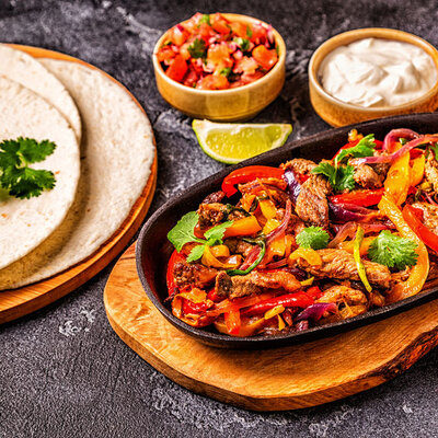 Fajitas are a popular dish in Tex-Mex cuisine made of grilled meat, which can be beef, chicken, or pork.