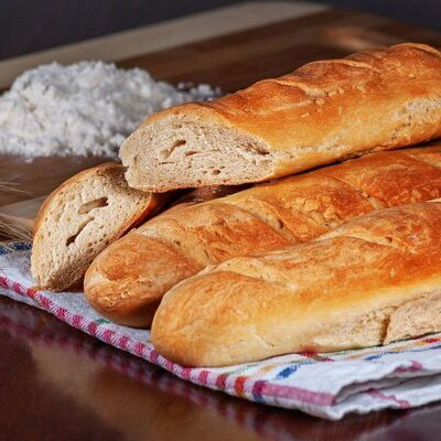 A French baguette is a long loaf of bread with a thin, crunchy crust that is traditionally produced in France.