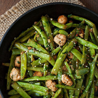 Green beans are a long, thin vegetable that grows on plants or vines.